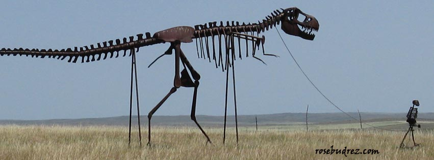 metal sculpture of a skeleton man leading a skeleton dinosauer.