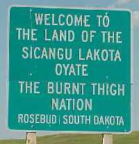 Highway sign: Welcome to the Land of the Sicangu Lakota Oyate the Burnt Thigh Nation. Rosebud, South Dakota.